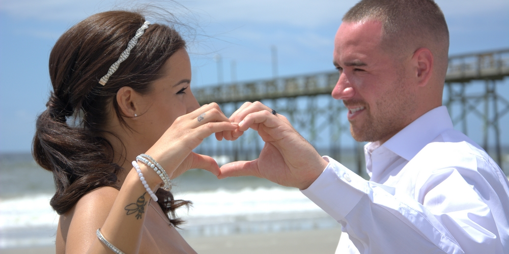 Myrtle Beach wedding newlyweds form a heart with their hands on the beach